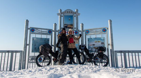 Kim and Bjørn pose for a photo under a sign in Kotzebue. After 36 days on the go they prepare to fly home.