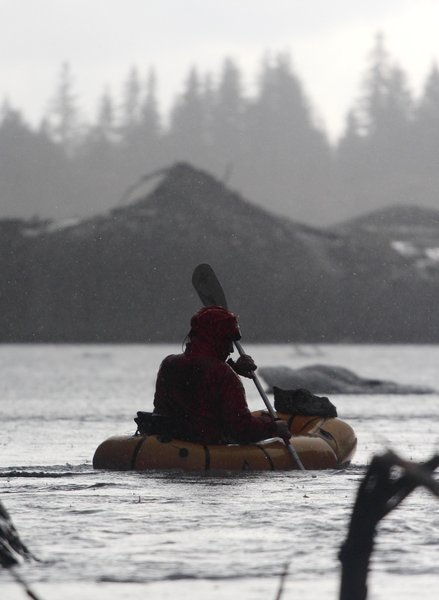 Visiting photographer Carl Donohue paddles his packraft in heavy rain.
