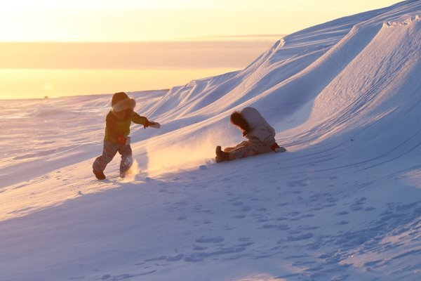 Kids playing on snowdrifts in the evening light
