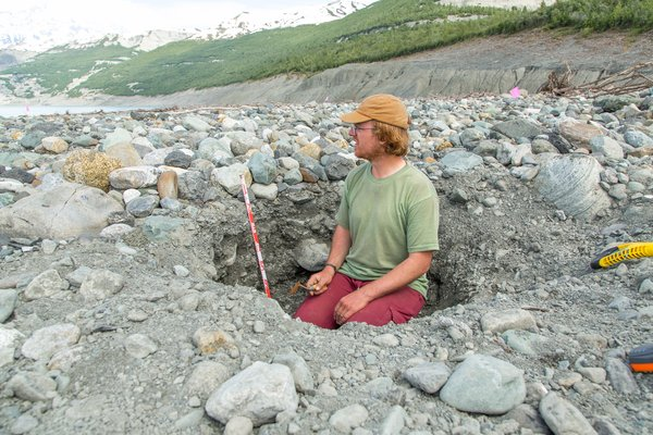Dr. Bretwood Higman inspects deposit layers in a trench. Over the three-week 'main expedition', in June 2016, to study the landslide and tsunami, in Taan Fjord, Dr. Higman dug many trenches to better understand the landslide generated tsunami.